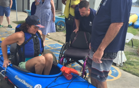A woman Veteran prepares to move from her adaptive kayak back into her wheelchair at the Summer Sports Clinic