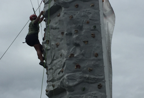 The author completes the rock climb at the Summer Sports Clinic