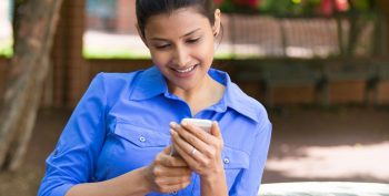 image of a young woman looking at her smart phone