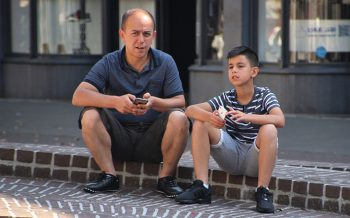 image of a man and boy sitting on a curb