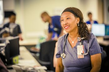 VA Nurse manages her nursing station and helps a community member