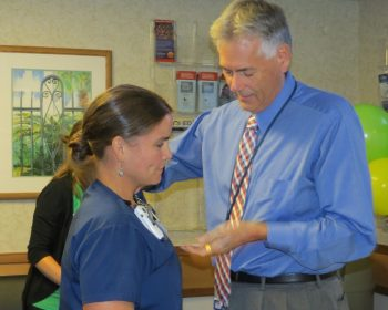 Martha Peak-Sweet, RN, is presented with her DAISY Award pin by John Goldizen, Associate Deputy of Nursing and Patient Care Services.