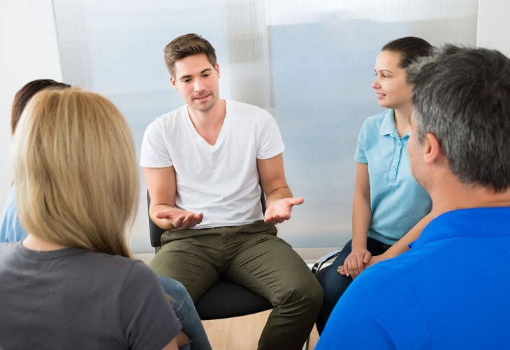 Image of a group therapy session featuring both men and women.