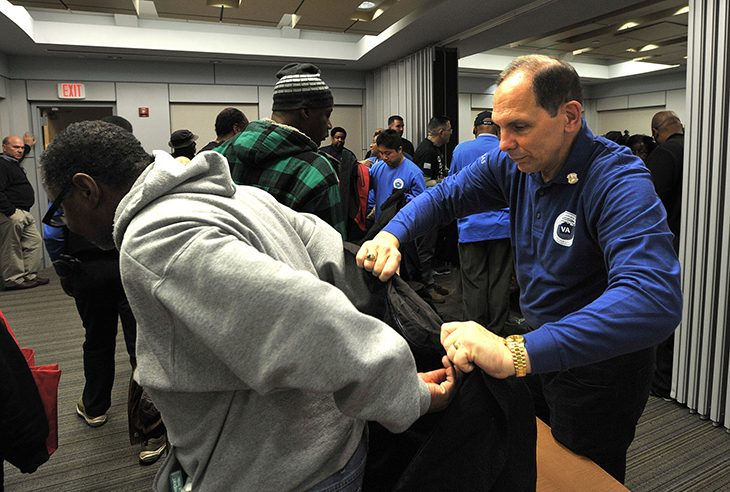 Secretary Bob McDonald helps a homeless man put on a new coat during the Washington DC VA Medical Center's Winterhaven Homeless Veterans Stand Down
