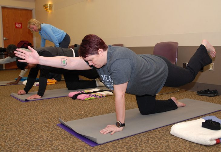 Veterans in the yoga study group work on perfecting a pose under the gentle guidance of Lead Yoga Therapist Nancy Schalk.