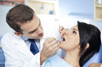 Image of a dentist examining a patient's teeth
