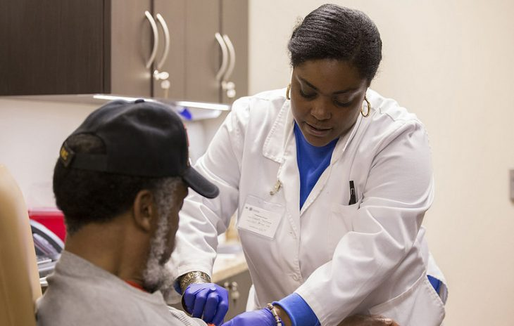 Image of a VHA medical staff member drawing blood from a Veteran in a clinical setting.