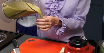 close up image of a person pouring a smoothie.