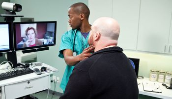 image of a health technician, a vetaan patient and a doctor appearing remotely via computer / video..