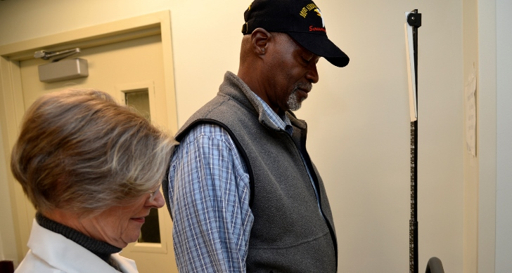 Image of Veteran Razzi Odom checks the scale while Becci Luhrs, MOVE! program coordinator, notes his progress toward his goal of dropping 31 pounds. Photo by James Arrowood.
