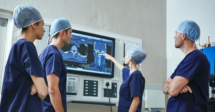 Surgeons reviewing x-ray of patient