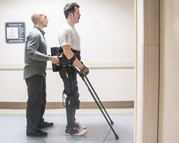 Veteran Brandon Myers participates in a trial of the exoskeleton brace with the help of physical therapist John Colaneri