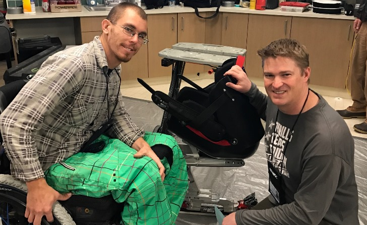 Image: John Ashbaugh gets fitted for his adaptive sports equipment with assistance from Chad Kincaid, a physical therapist and prosthetist helping at the seating/technology/boot fit clinic.