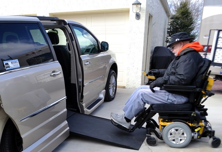 An elderly male Veteran in a wheelchair, entering a van.