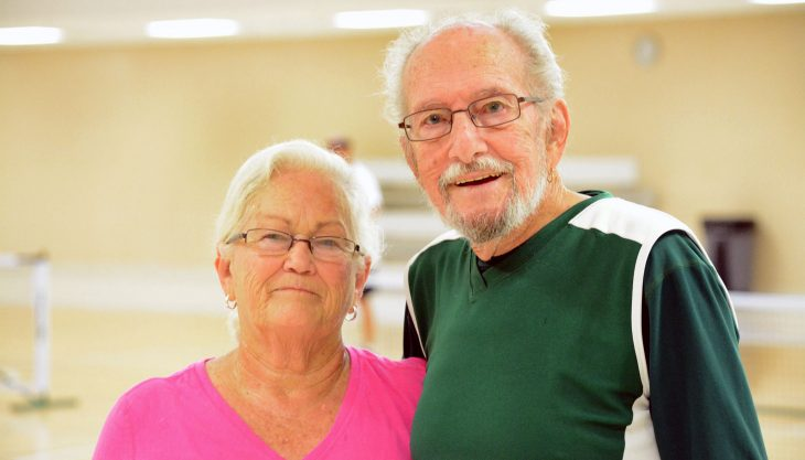 Husband and wife standing in gym.