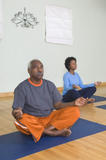 Senior Man Meditating in Yoga Class