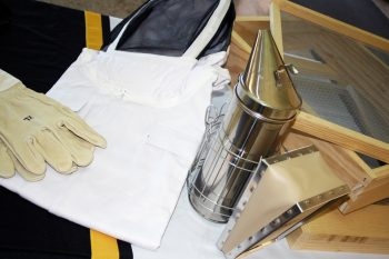 A number of tools for beekeeping including gloves, screens, and a smoker displayed on a table.