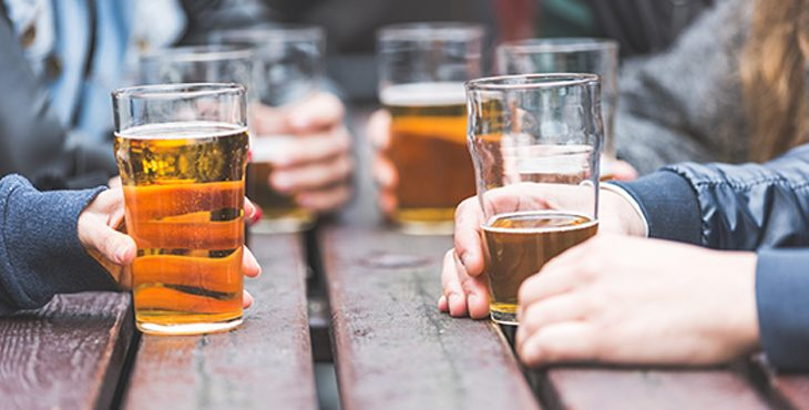 IMage of hands holding beer glasses on a picnic table.