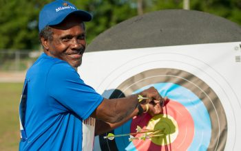 man pulling arrows from archery target
