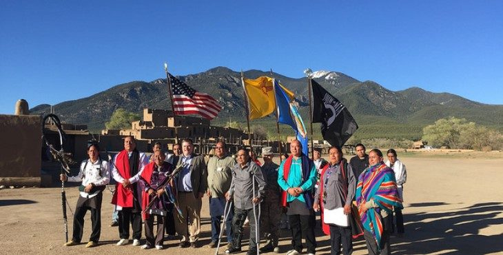 Image: VA officials with tribals members with the mountains in the background.