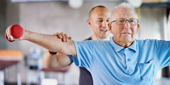 Image of a physiotherapist helping a senior man with weights