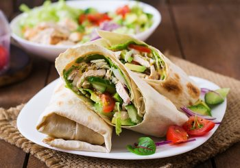 Fresh tortilla wraps with chicken and fresh vegetables on plate