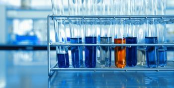 orange and blue chemical solution in test tubes in metal rack science lab
