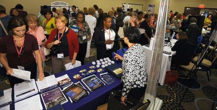 Images of women viewing static displays at a conference