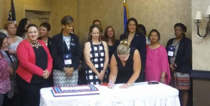 Image: Group of women behind a table observing the signing of the agreement.