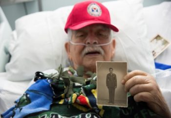 Image of Fidel Gomez holding a picture of himself in uniform