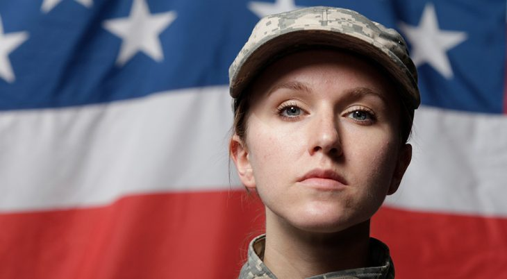 Female solider standing in front of American Flag