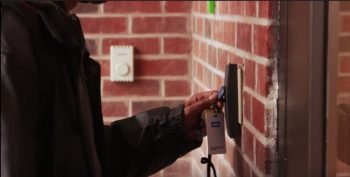 IMAGE: An unidentified person using a key fob to enter into a building building