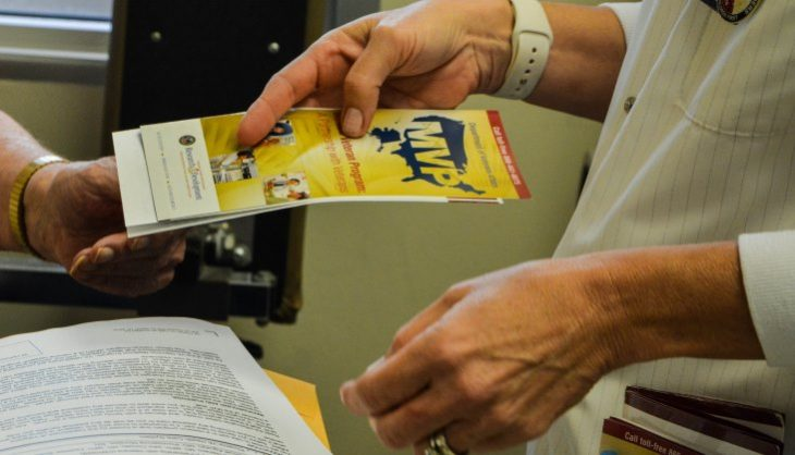 image: Annette Videla, a registered nurse and research coordinator with the Phoenix VA Health Care System's Million Veteran Program, provides a volunteer a pamphlet explaining the MVP. The Phoenix VA recently surpassed its goal of recruiting 20,000 volunteers into the MVP.
