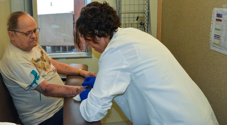 image: Annette Videla, a registered nurse and research coordinator with the Phoenix VA Health Care System's Million Veteran Program, prepares to extract blood from a volunteer. The Phoenix VA surpassed its goal of recruiting 20,000 volunteers for the nationwide initiative.