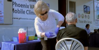 IMAGE: A VA employee gives a Veteran a shot outside of a VA monile clinic.