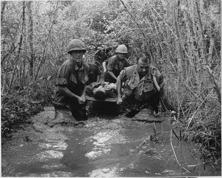 Four soldiers carry their wounded comrade on a stretcher through a swamp in the