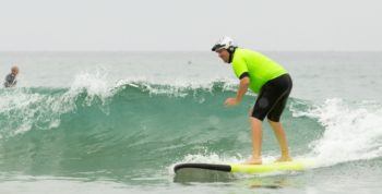 IMAGE: Jason Pilarski rides a surf board at the Summer Sports Clinic.