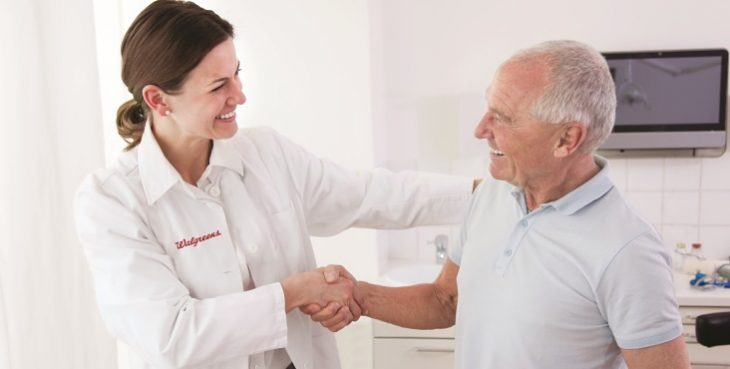 Image: A Walgreens employee in a white coat shaking hands with an older man or a flu shot.