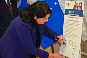 Rima Nelson, PVAHCS director, signs a commitment pledge indicating the Phoenix VA is committed to curbing Veteran suicide.