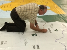 IMAGE: Veterans, families, and friends signed a large-scale movable map of the war theater in honor or memory of military service.