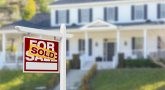 """Sold placard on house """"for sale"""" sign in front of house"""