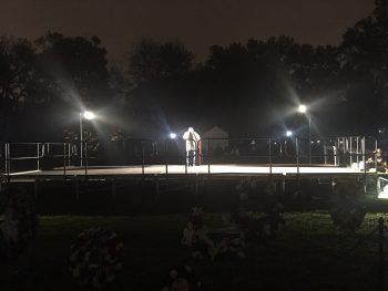 Man stands center stage to read 30 names from the wall