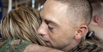 Image: A service member huging thier spouse.g