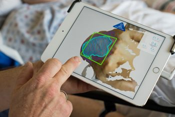 A nurse demonstrates 3-D imaging of a wound on a tablet