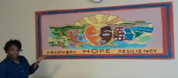 Kimberly White, RN,  Recovery Coach, PRRC/ Mental Health, with  mural