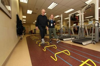 "Donald Salganik, who served in the Air Force during the Korean War, proceeds through an obstacle course that is part of the ""multimodal balance intervention"" being studied by Baltimore VA researchers. With him is study coordinator Lydia Paden."