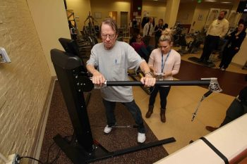 Roger Bergeron, who served in the navy, works his hip abductors as exercise physiologist     Katie Dondero adjusts the machine settings.