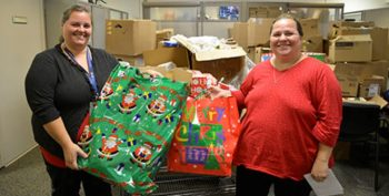 IMAGE: Voluntary Service Specialist Candy Anderson presents Cathy Adkins, spouse of Veteran Thomas Adkins, Sr., with gifts for her children that were donated through Voluntary Service's Angel Tree program. Photo by Meredith A. Hagen.