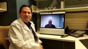 Telehealth practitioner Dr. Paul Maas (foreground) is joined via video by Rod Miles, facility telehealth coordinator at Bay Pines VA Healthcare System.