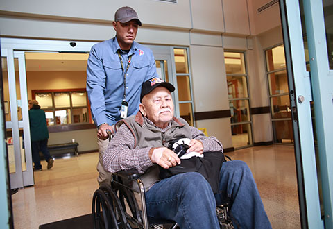 Mr. Roberto Garza-Rivera a Veteran Transportation Service (VTS) driver helps disabled, Korean War Veteran Mr. Francisco Galvan by pushing him and his wheelchair through the main entrance of the VA Harlingen Outpatient Clinic, Nov. 20, 2017.
